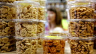 Young woman purchases dried fruits and nuts in grocery video