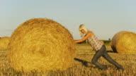 HD: Young Woman Pushing Hay Bale video