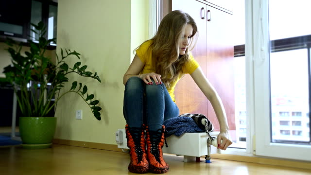 Young woman put,cap on sitting on cold radiator video