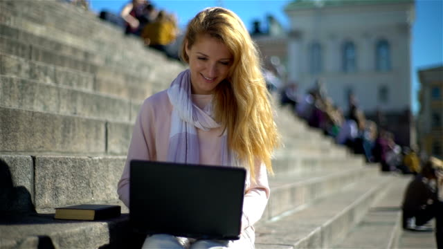 Young woman puts aside the laptop and picks up a book on the stairs in the center of the city. Slow motion. video