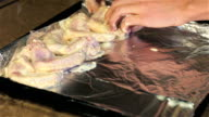 Young woman puts chicken wings on baking sheet with foil video