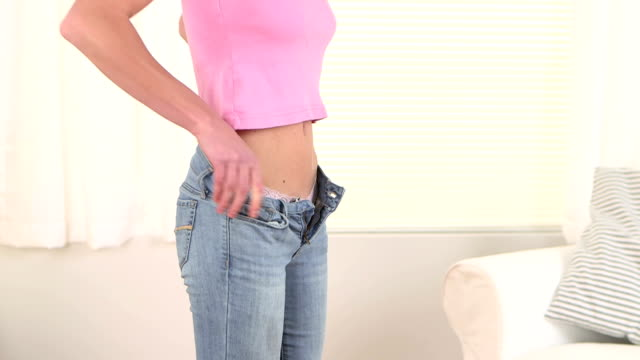 Young woman putting on pants video