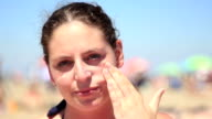 Young woman putting sunscreen to her face video