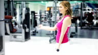 Young woman raises hand weights at the gym. video