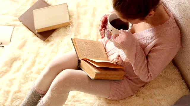 Young woman reading a book and drinking coffee video