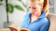 Young woman reading a book at home. video