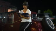 Young woman reading a book beside the classic car. video