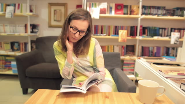 Young woman reading a book in a library store. video