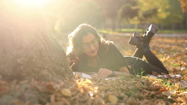 Young woman reading a book in the park video