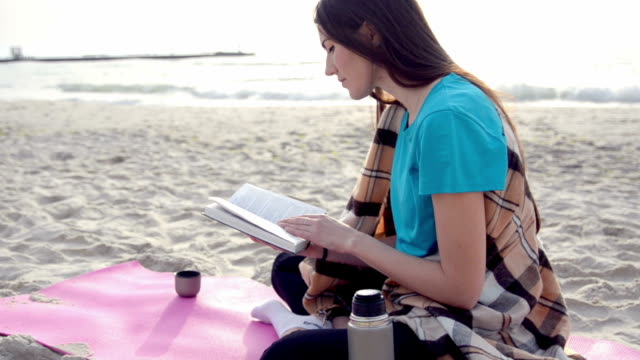 Young Woman Reading a Book on beach drinking hot tea or coffee from thermos video