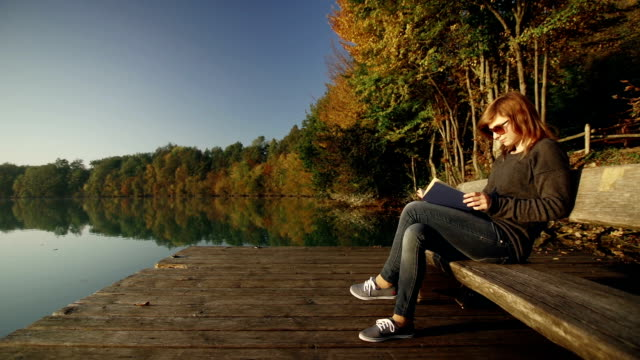 Young woman reading a book on bench by the lake video