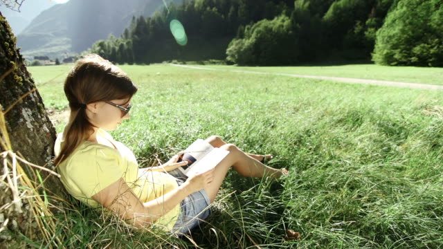 Young woman reading a book under a tree video