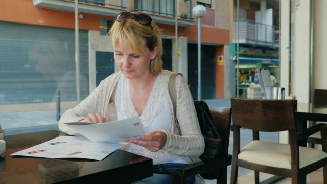 Young woman reading a menu in a cafe video
