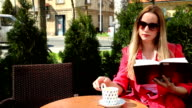 Young woman reading book and drinking beverage video
