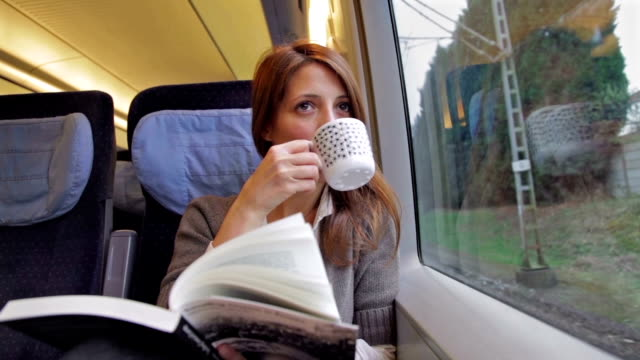 Young woman reading book and drinking coffee on train video