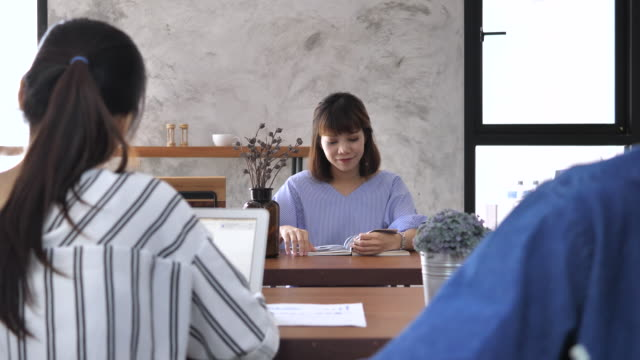 Young woman reading book at a cafe video
