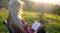 Young woman reading book in nature video