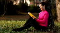 young woman reading book in the green park video