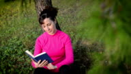 young woman reading book in the nature video