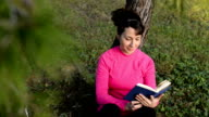 young woman reading book in the park video