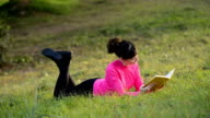 young woman reading book lying in the meadow video