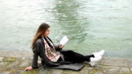Young woman reading book on seine river coastline video