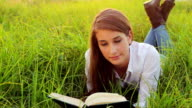 Young Woman Reading Book Outside in Nature video