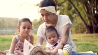 Young woman reading book with her children in the park video