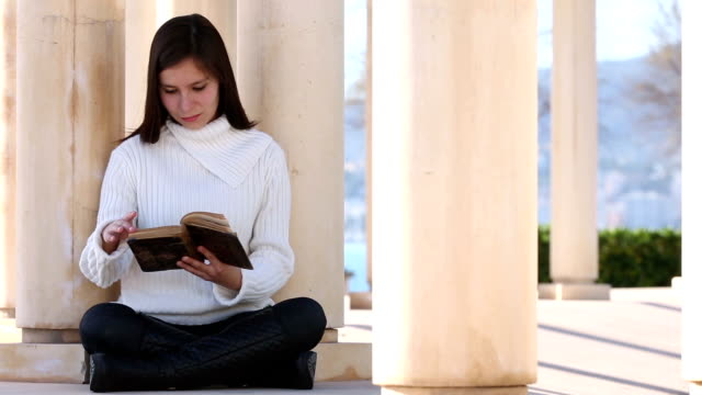 Young woman reading old book outside video