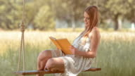 SLO MO Young woman reading on a swing in nature video