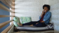 Young Woman Reclining on Couch Talking on Phone video