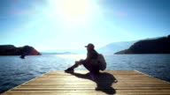 Young woman relax sitting on pier at the lake video