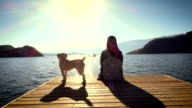 Young woman relax sitting on pier at the lake with dog video