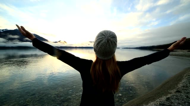 Young woman relaxes by the lake in Autumn video