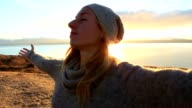 Young woman relaxes by the lake, stands arms outstretched video