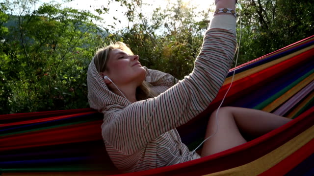 Young woman relaxes in hammock, listens to mp3 player video