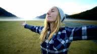 Young woman relaxes in nature, arms outstretched video