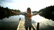 Young woman relaxes on lake pier, stands arms outstretched video