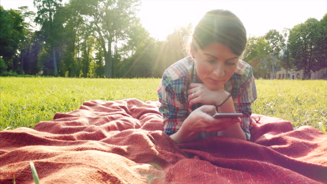 Young woman relaxing and using a smart phone. video