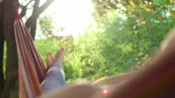 Young woman relaxing in a hammock under the trees video
