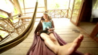 Young woman relaxing on hammock with kitty video