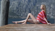 Young woman relaxing on landing stage video