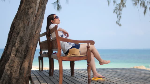 Young woman relaxing on the beach near the sea in summer time , relaxation concept , 4k(UHD) video