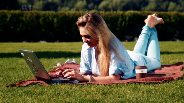 Young woman relaxing with her laptop on the grass video