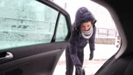 Young woman removing the snow from a car. video