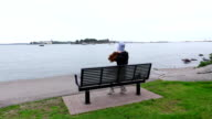 Young woman rest on bench at gulf shore, feel cold and put on hipster hat video