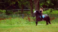 Young woman riding horse on ranch video