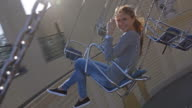 Young woman riding on chairoplane in an amusement park video