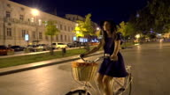 Young woman riding on old vintage bike at city center, slow motion video