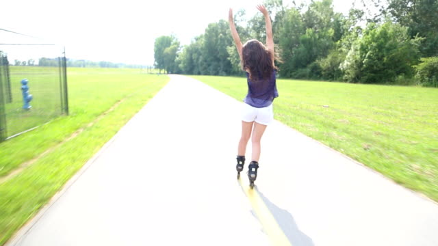 Young woman rollerblading in park from back with hands in the air video